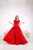 Elegant woman in a long red dress is standing in a white room, d Stock Image