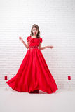 Elegant woman in a long red dress is standing in a white room, d Stock Images