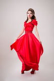 Elegant woman in a long red dress is standing in a white room, d Royalty Free Stock Images