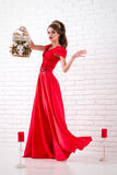 Elegant woman in a long red dress is standing in a white room an Stock Images