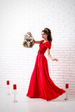 Elegant woman in a long red dress is standing in a white room an Royalty Free Stock Photos
