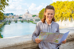 Elegant woman looking at map of Rome by Tiber River Stock Images