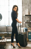 Elegant woman with luggage in loft apartment ready for departure Royalty Free Stock Images