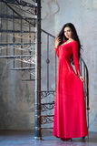 Elegant woman in luxury long violet dress standing near stairs Royalty Free Stock Photography
