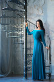 Elegant woman in luxury long violet dress standing near stairs Royalty Free Stock Photos