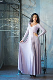 Elegant woman in luxury long violet dress standing near stairs Royalty Free Stock Images