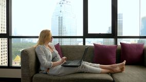 An elegant woman is lying on a sofa by the panoramic window overlooking the skyscrapers and using her laptop royalty free stock photo