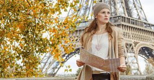 Elegant woman with map looking into the distance in Paris Stock Photo