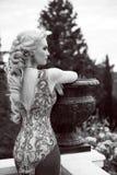 Elegant woman in mermaid gorgeous dress at park. Wedding hairsty Royalty Free Stock Image