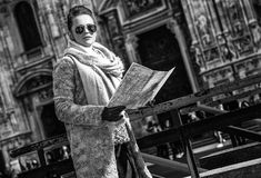Elegant woman in Milan, Italy with map looking into distance Royalty Free Stock Photos