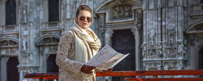 Elegant woman in Milan, Italy with map looking into distance Royalty Free Stock Photography