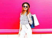 Elegant woman model with shopping bags wearing a black hat. White pants over colorful pink background stock photos