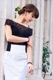 Elegant woman near columns. Portrait of beautiful young brunette fashion female woman wearing black lace top and white skirt and with her hair done in Greek Stock Photography