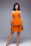 Elegant woman in orange dress full body shot Stock Photo
