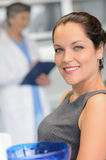 Elegant woman patient at dentist surgery smiling. Elegant women patient at dental surgery smiling dentist in background Royalty Free Stock Photography