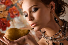 Elegant woman with pear. A portrait of an elegant, fashionable woman, holding a pear in one hand Stock Image