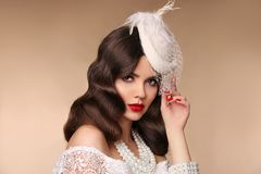 Elegant woman portrait in retro hat. Beautiful girl wears in pea. Rls jewelry, wavy hairstyle and red lips makeup. Brunette lady isolated beige background Royalty Free Stock Image