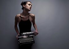 Elegant woman pose with ancient typewriter. Stock Photography
