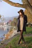 Elegant woman poses in autumn clothing. Beautiful and elegant woman poses in autumn clothing  . Warm sunset light Stock Photos
