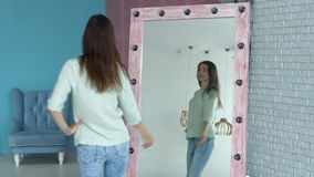 Elegant woman posing in front of mirror at home stock footage