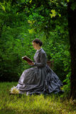 Elegant Woman Reads Outdoors Wearing Historical Clothing Stock Images