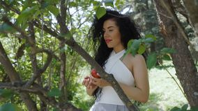 Elegant woman with red apple in the garden. Beautiful woman in dress holds red apple in hands and posing for camera. Charming brunette enjoys a fruit and leans stock video