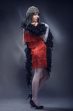 Elegant woman in the red dress and feather boa Royalty Free Stock Photography