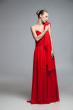 Elegant woman in red dress holding cloth on shoulder Royalty Free Stock Photo