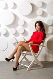 Elegant woman in red dress posing in white wooden chair Royalty Free Stock Photo