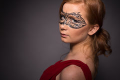 Elegant woman in a red dress. Sensual beauty lovely makeup mask mysterious art Royalty Free Stock Photography