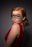 Elegant woman in a red dress. Sensual beauty lovely makeup mask mysterious art Royalty Free Stock Image