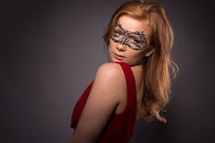 Elegant woman in a red dress. Sensual beauty lovely makeup mask mysterious art Stock Image