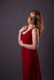 Elegant woman in a red dress. Sensual beauty lovely makeup mask mysterious art Stock Images
