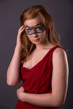 Elegant woman in a red dress. Sensual beauty lovely makeup mask mysterious art Stock Photo