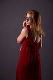 Elegant woman in a red dress. Sensual beauty lovely makeup mask mysterious art Royalty Free Stock Photo