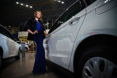 Elegant woman with red hair in blue dress and fur coat standing near new modern car Stock Photo