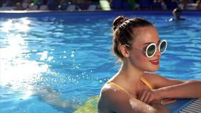Elegant woman rests in the pool and enjoys swimming in the water, summer rest stock footage