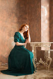 Elegant woman in retro style sitting at the table.Elegant sad woman in retro style. Depression stock photo