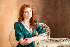 Elegant woman in retro style sitting at the table. Green dress Stock Photography