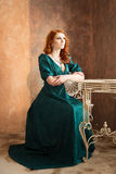 Elegant woman in retro style sitting at the table. Green dress Stock Images