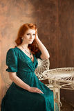 Elegant woman in retro style sitting at the table. Green dress Stock Photo
