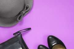 Woman`s accessories for autumn. Black leather purse, black shoes and grey hat. Copy space for text stock photo