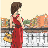 Elegant woman. Series Urban fashion. Street panorama, architectural structures, bridges. Elegant lady in red dress stands by the parapet Royalty Free Stock Photo