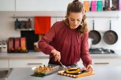 Elegant woman serving pumpkin in modern kitchen Stock Images