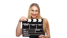 Elegant woman with red lips go, using clapper board and smiling, on white