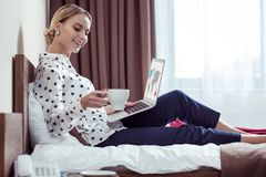 Elegant woman shilling with coffee on hotel bed after meetings. Chilling in hotel. Elegant blonde-haired businesswoman shilling with coffee on hotel bed after stock photos