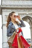 Elegant woman shopper near Arc de Triomphe looking into distance. Stylish Christmas in Paris. smiling elegant woman in trench coat with shopping bags and Royalty Free Stock Photography