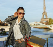 Elegant woman with shopping bags looking aside near Eiffel tower Stock Photos