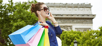 Elegant woman with shopping bags using mobile on Champ Elysees. Get your bags ready for the Paris shopping. happy young elegant woman in sunglasses using a cell stock photos