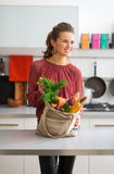 An elegant woman is showing off her bag of fresh autumn veggies Royalty Free Stock Photo